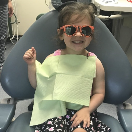 little girl smiles big for her first visit to the pediatric dentist in Salem NH. she is sitting on a dental chair, wearing pink sunglasses and a green dentist bib.